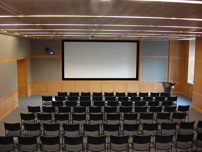 A large, comfortable, carpeted, modern, lecture hall with blonde wood and grey fabric paneling; the room is set with rows of chairs facing a large projection screen