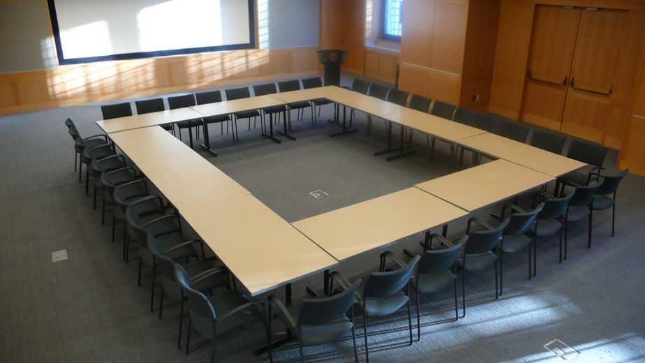 A large, comfortable, carpeted, modern, lecture hall with blonde wood and grey fabric paneling; the room is set with long tables in an enclosed rectangular shape and chairs on the perimeter