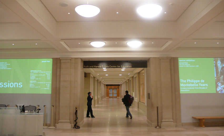 The entryway to long, brightly lit corridor with white stone flooring and light beige fabric walls; on the walls on either side of the entryway are projections of white text on a green background