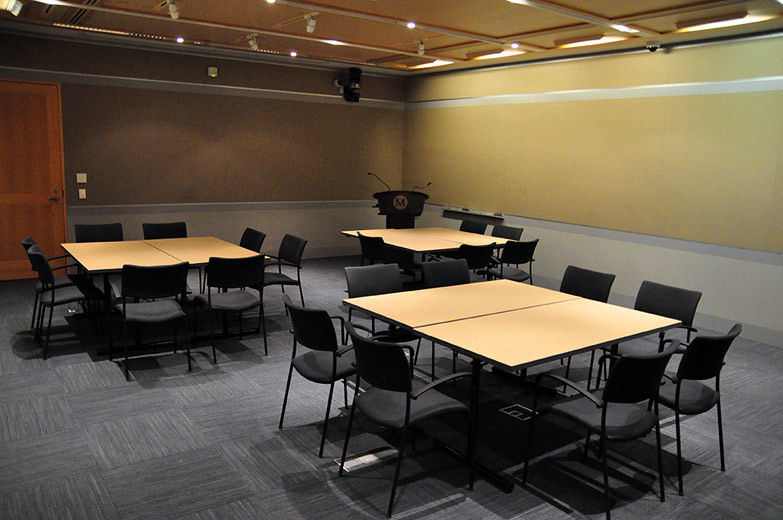 A small, comfortable, modern, carpeted room with gray fabricwalls and gray paneling; the room is set with three groupings tables with chairs