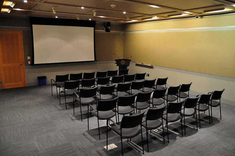 A small, comfortable, modern, carpeted room with gray fabricwalls and gray paneling; the room is set with rows of chairs facing a projection screen and lectern