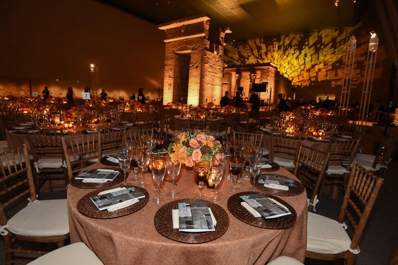 Large glass-enclosed gallery with an ancient Egyptian sandstone temple at night, lit with dramatic lighting for a party; the room is set with large round tables decorated with elegant flower arrangements, a formal service, and candles
