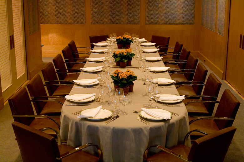 A casual-elegant private dining room with blond wood paneling and fabric covered walls, leather and chrome chairs; the table is set for eighteen with a casual service and low, elegant flower arrangements
