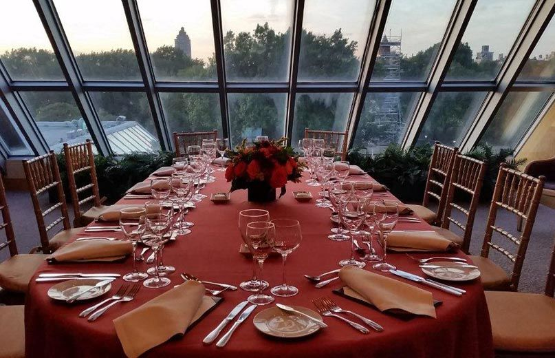 An intimate and elegant glass-enclosed room; a dining room table covered in a dark red table cloth is set with an elegant yet casual service and a low, elegant flower arrangement