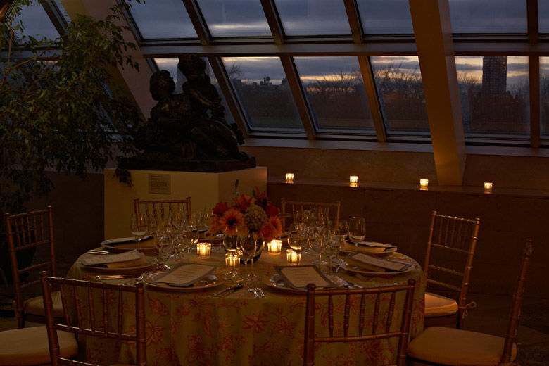 A intimate, dimly lit, glass-enclosed dining room with a round dining table set with a formal service, votive candles, and a low, colorful flower arrangement