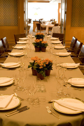 A casual-elegant private dining room with blond wood paneling and fabric covered walls, leather and chrome chairs; the table is set for fourteen with a casual service and simple potted-flower arrangements