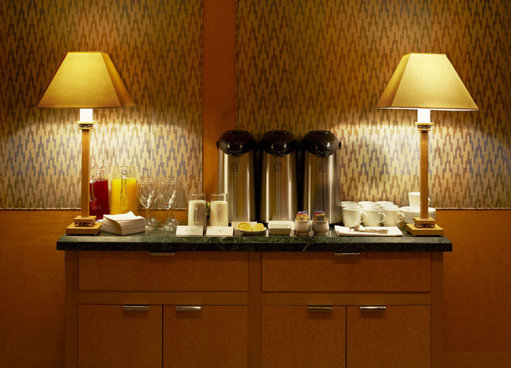 An elegant and simple sideboard with two lamps set with a full coffee and tea service, in a private dining room with blond wood paneling and fabric covered walls