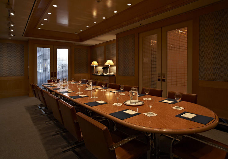 A casual-elegant private dining room with blond wood paneling and fabric covered walls, leather and chrome chairs; the table is set sparingly with glasses and pitchers of water