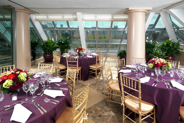 A bright, sunlit interior terrace set with round dining tables draped in dark purple table cloths and casual table service