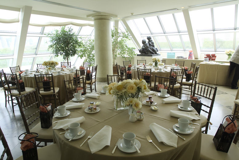 A bright, sunlit interior terrace set with large round dining tables draped in light green table cloths, with a casual table service and pale yellow flower arrangements