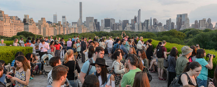 View of a crowd of people on The Met's Cantor Roof Garden against a backdrop of the Manhattan skyline