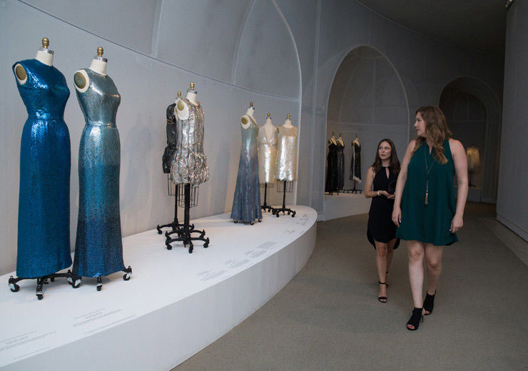 Two women walking through the Manus x Machina exhibition