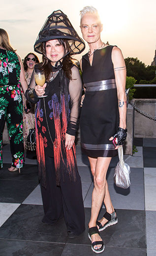 Two women pose at The Met Young Members Party