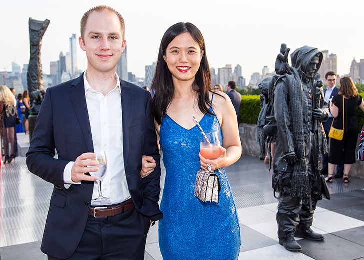 Two people pose at The Met Young Members Party