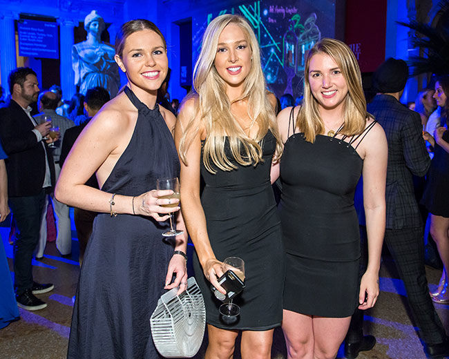 Three women pose at The Met Young Members party