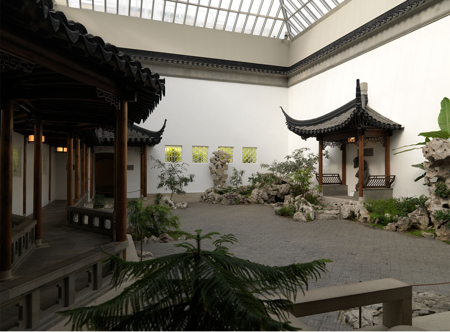 An interior courtyard with pagodas, plantings, ornamental rocks, and a fish pond