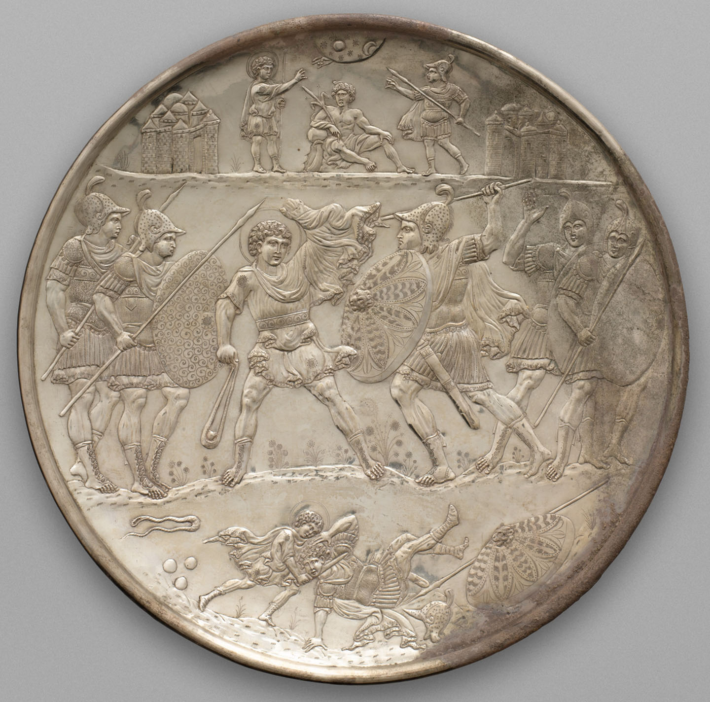 A large silver plate decorated in relief of two armies engaged in battle
