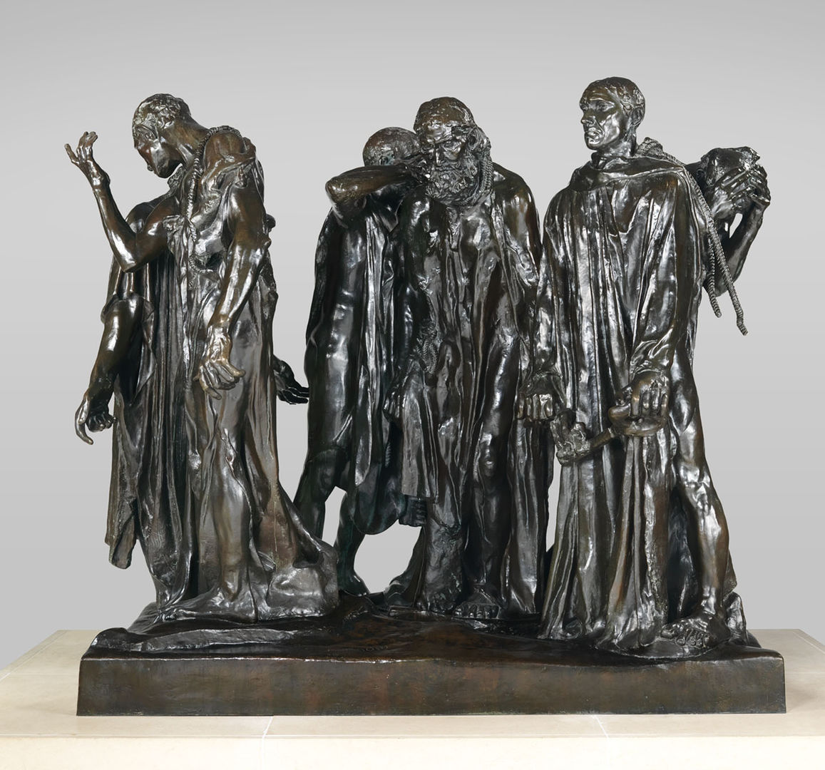 An over-life size bronze sculpture of a group of men chained together in a group, walking in a circle