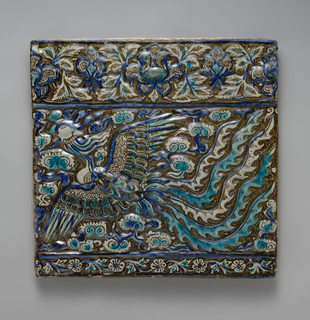 A square ceramic tile decorated in raised relief with a phoenix glazed in cobalt blue, turquoise, and white, flying through stylized swirling clouds