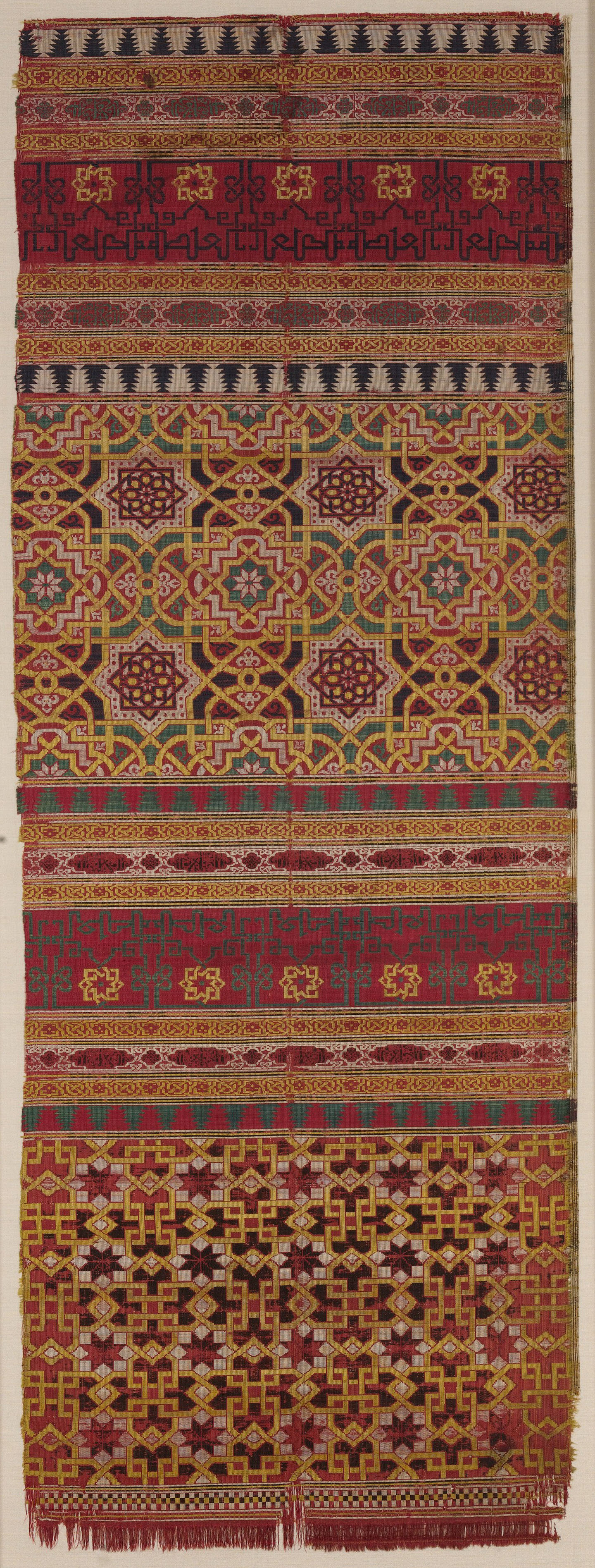 A textile woven with an intricate geometric pattern of yellow, purple, white and green