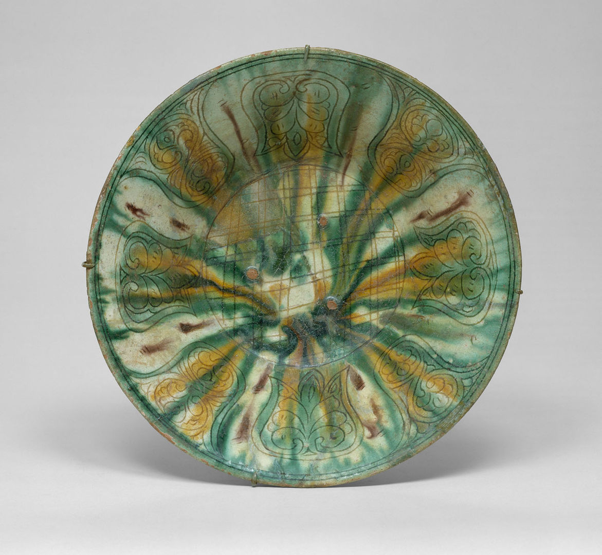 A ceramic bowl with a white ground and decorated with green, yellow, and red dripping glaze