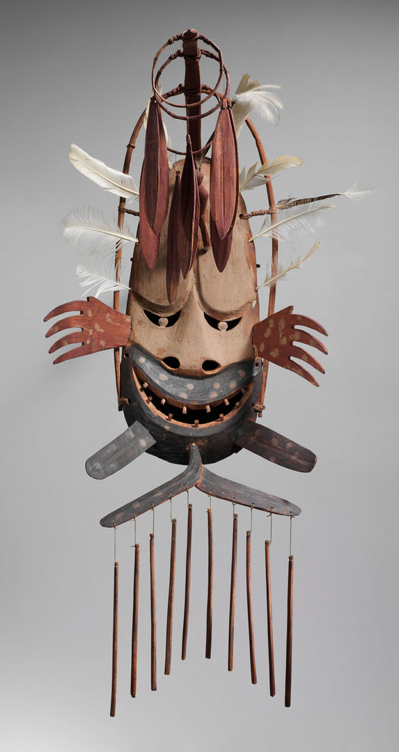 An indigenous Alaskan mask with a ferocious smile decorated with hanging wind chimes, feathers, and charms