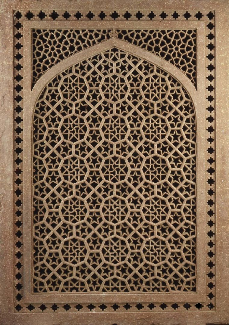 A sandstone window screen, pierced and carved in an intricate geometric pattern