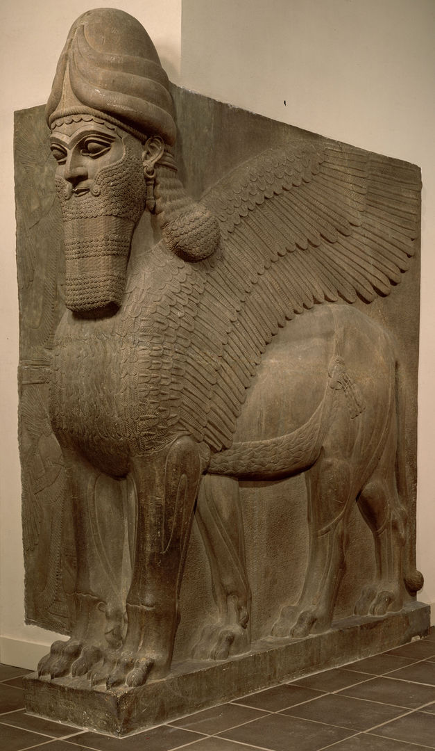 A colossal gray stone sculpture of a winged, human-headed lion-like animal deity with a long luxurious beard and hair, wearing a pointed crown