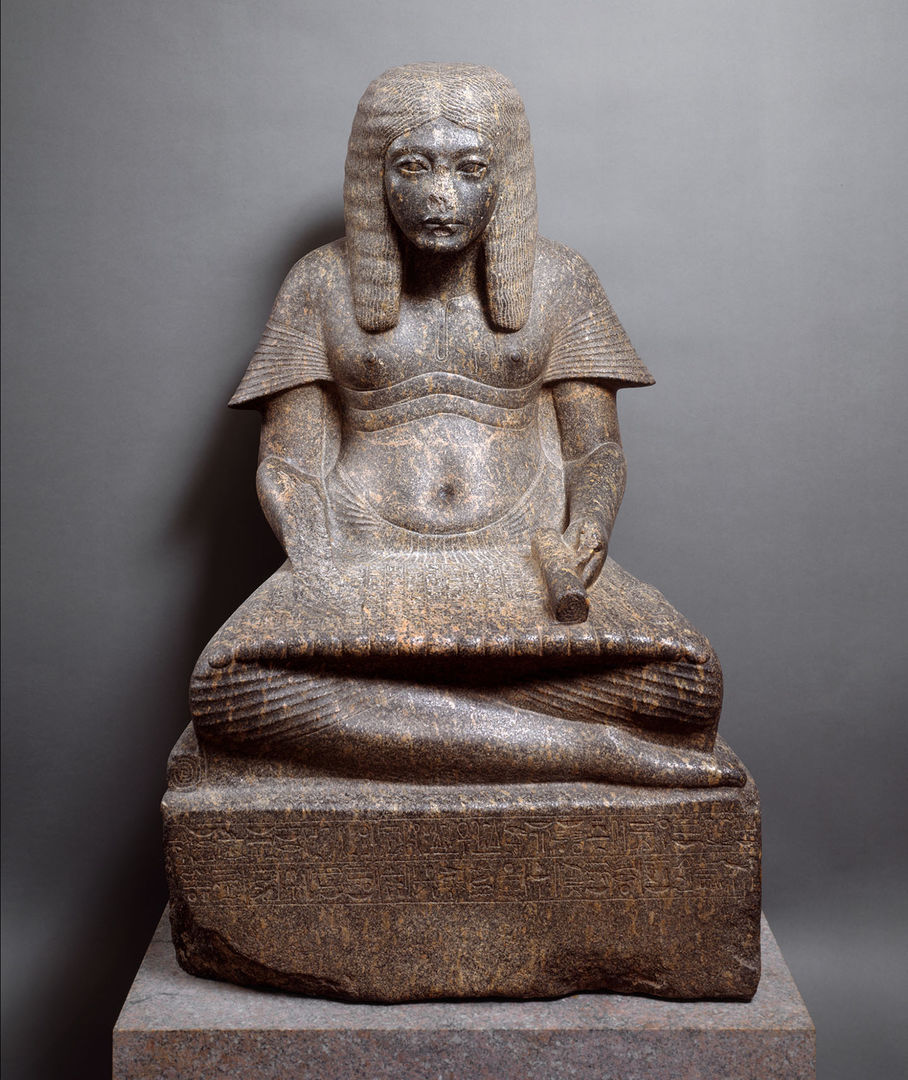 A dark-gray stone sculpture of an ancient Egyptian man with a grim face, sitting on a plinth cross-legged with his hands in his lap