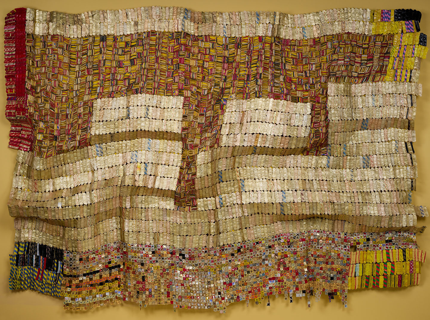 A huge coloful tapestry made of woven copper wire strung with found aluminum bottlecaps