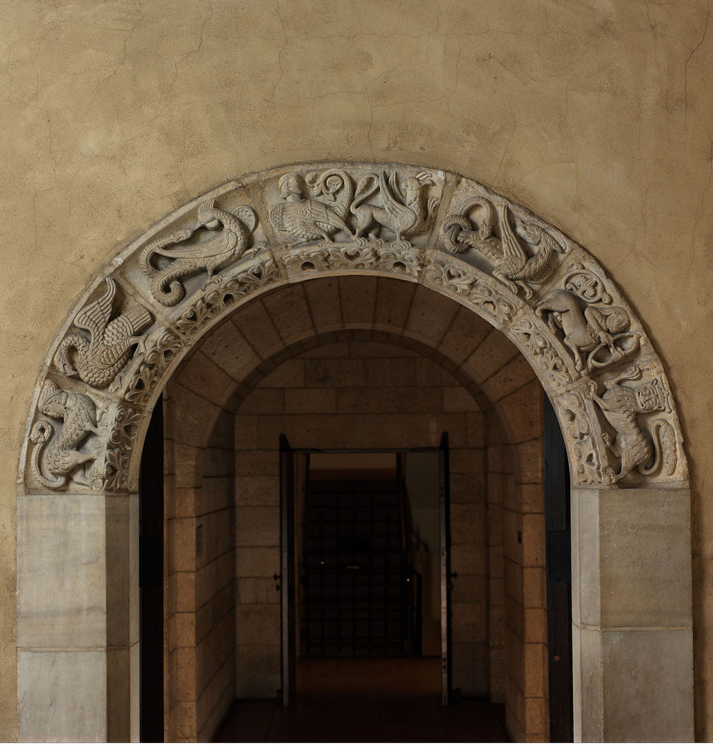A stone arched doorway with seven fantastic animals carved in relief bordering the arch