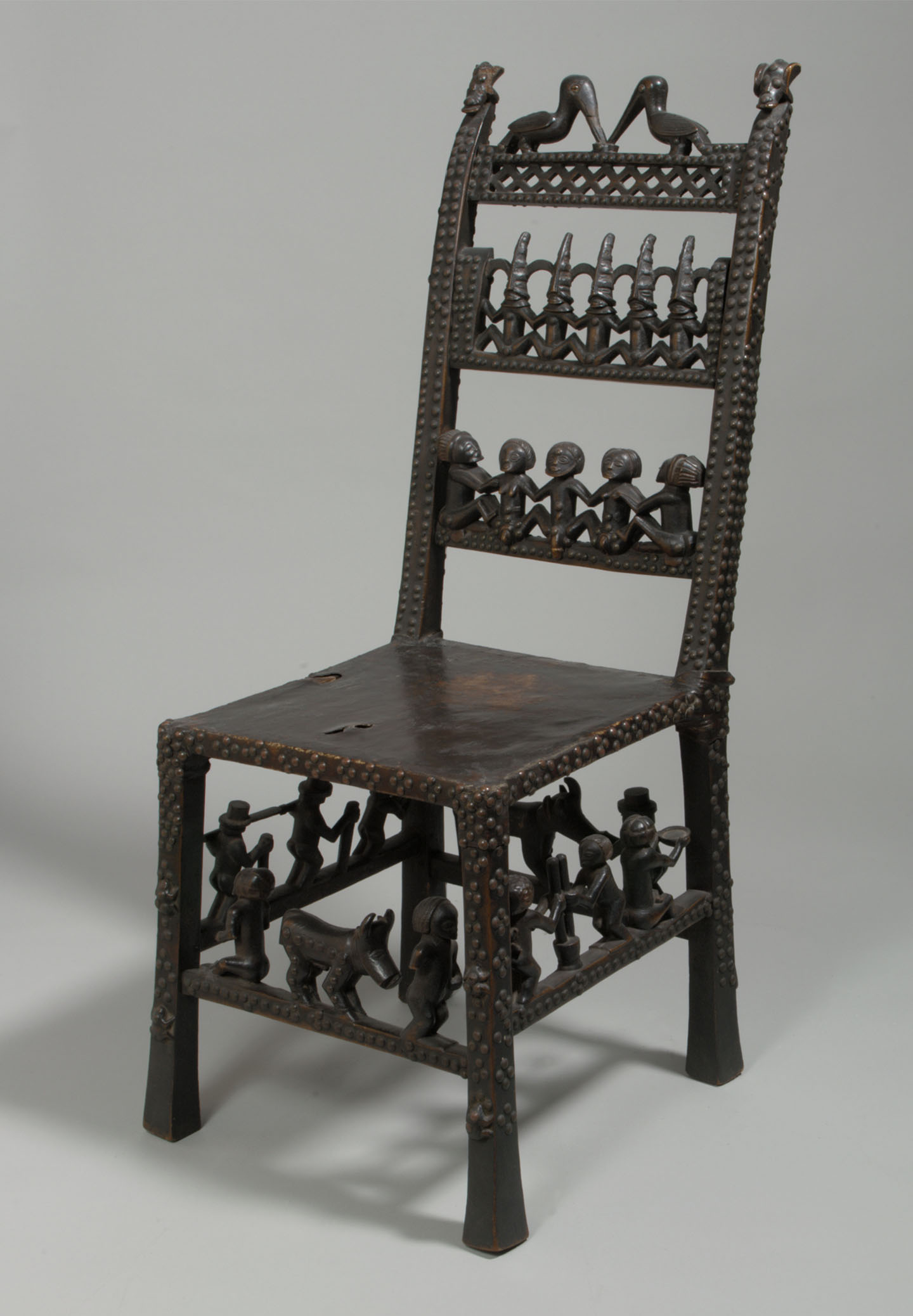 A dark wood African side chair decorated with seated figures and animals on the chair back, and on the rungs between the legs