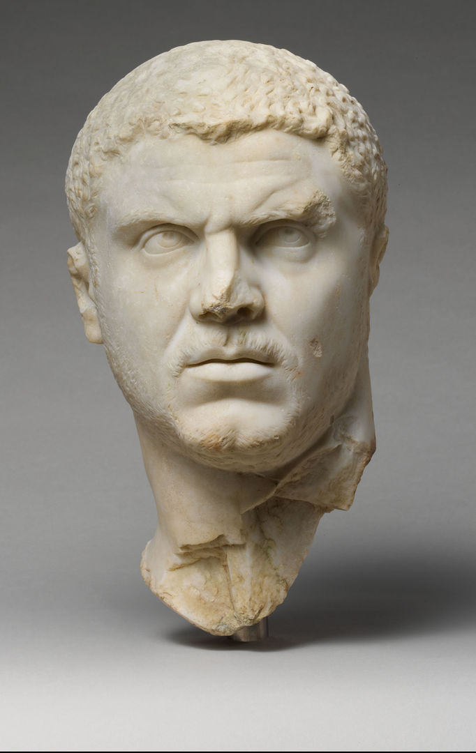 A white stone portrait bust of a very serious-looking man, with furrowed brow and intense gaze