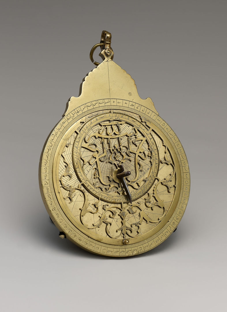 A scientific instrument constructed of brass circular plates placed one on top of the other, which can be slid and rotated; the brass is intricately pierced and engraved with Arabic calligraphy and floral motifs