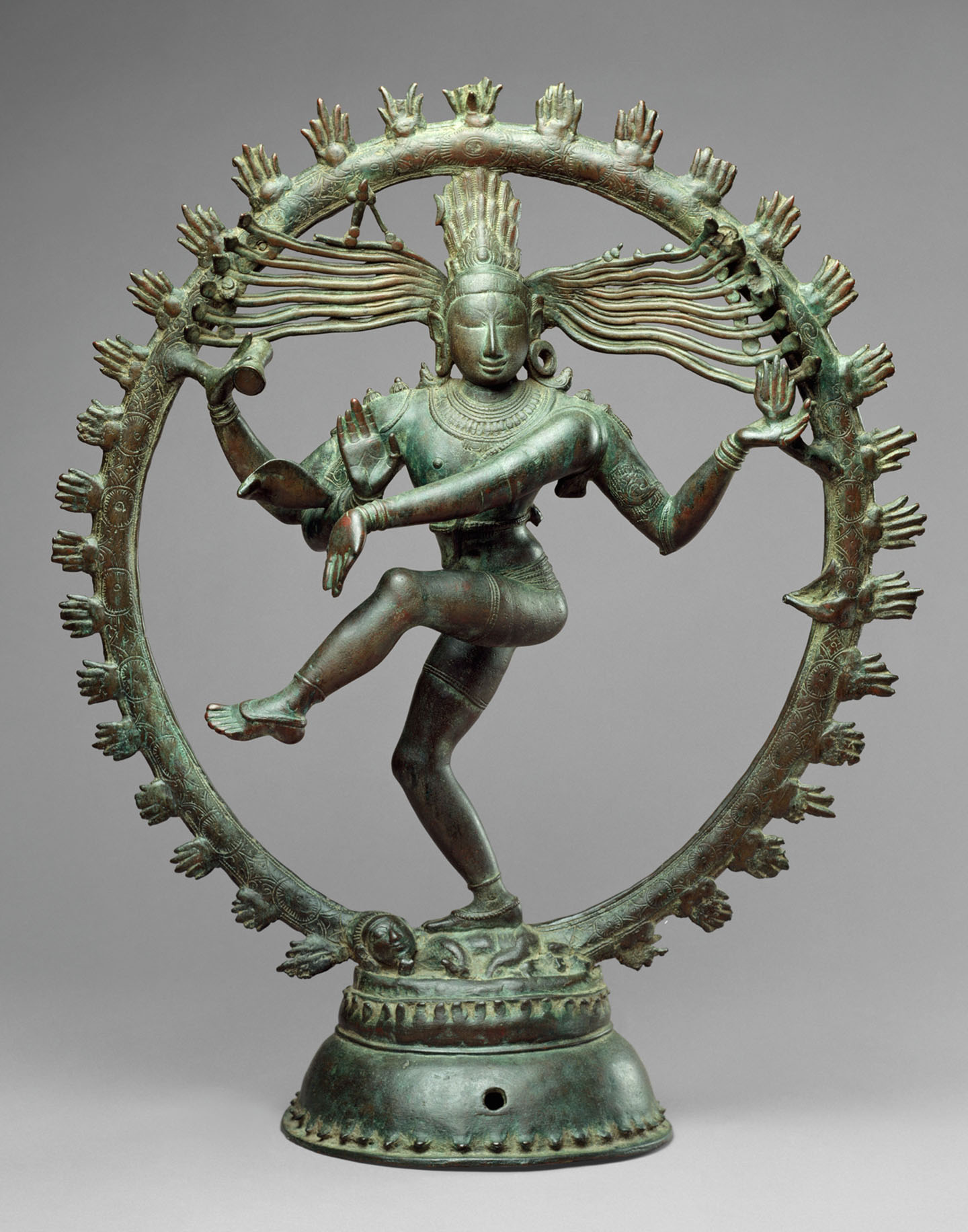 An oxidized copper sculpture of an Indian deity with four arms, standing on one leg dancing, encircled by a ring of stylized fire