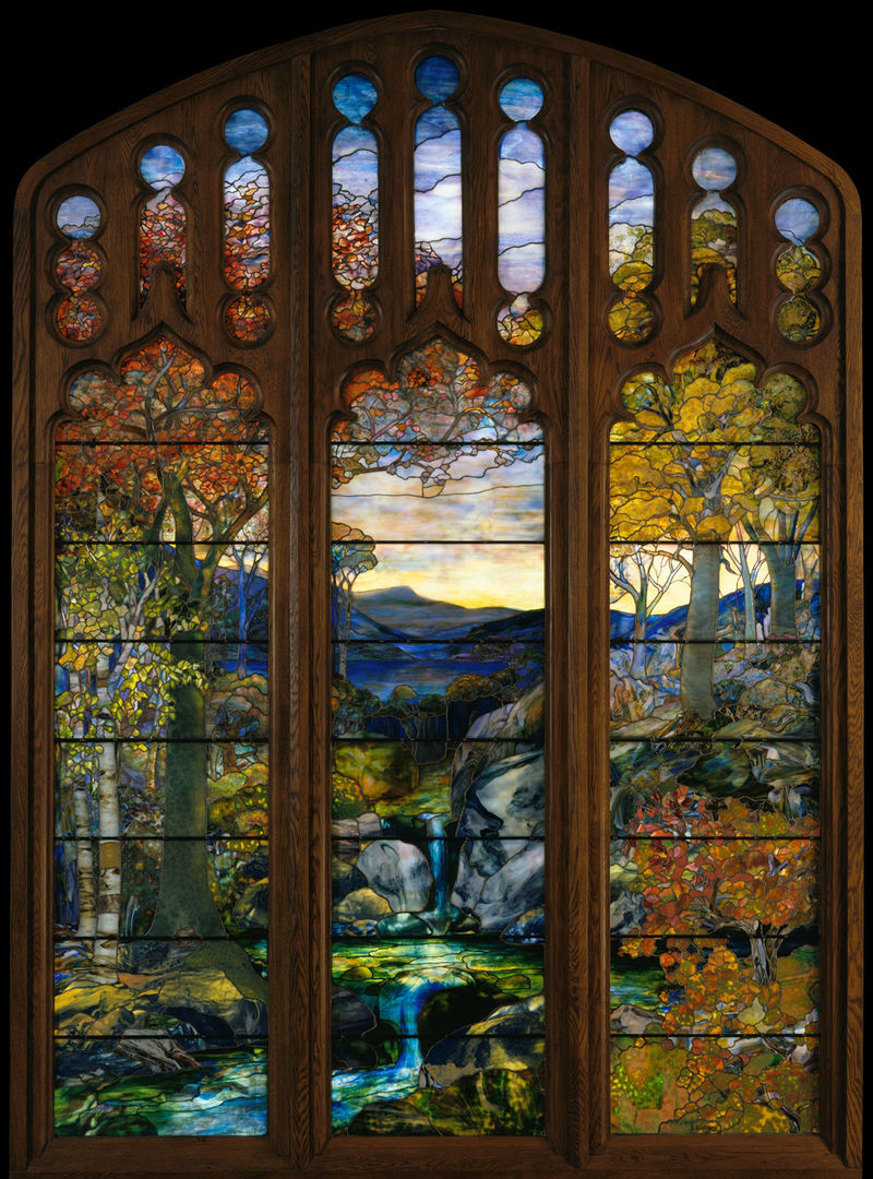 A large stained glass window in a dark wood pointed-arched window frame depicting an autumn landscape with distant mountains and a flowing stream in the foreground