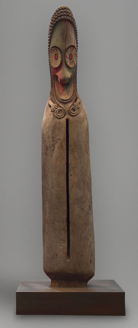 A hollow, wooden Oceanic sculpture with a bird-like face, large round eyes, sharp down-turned beak, and pointed head