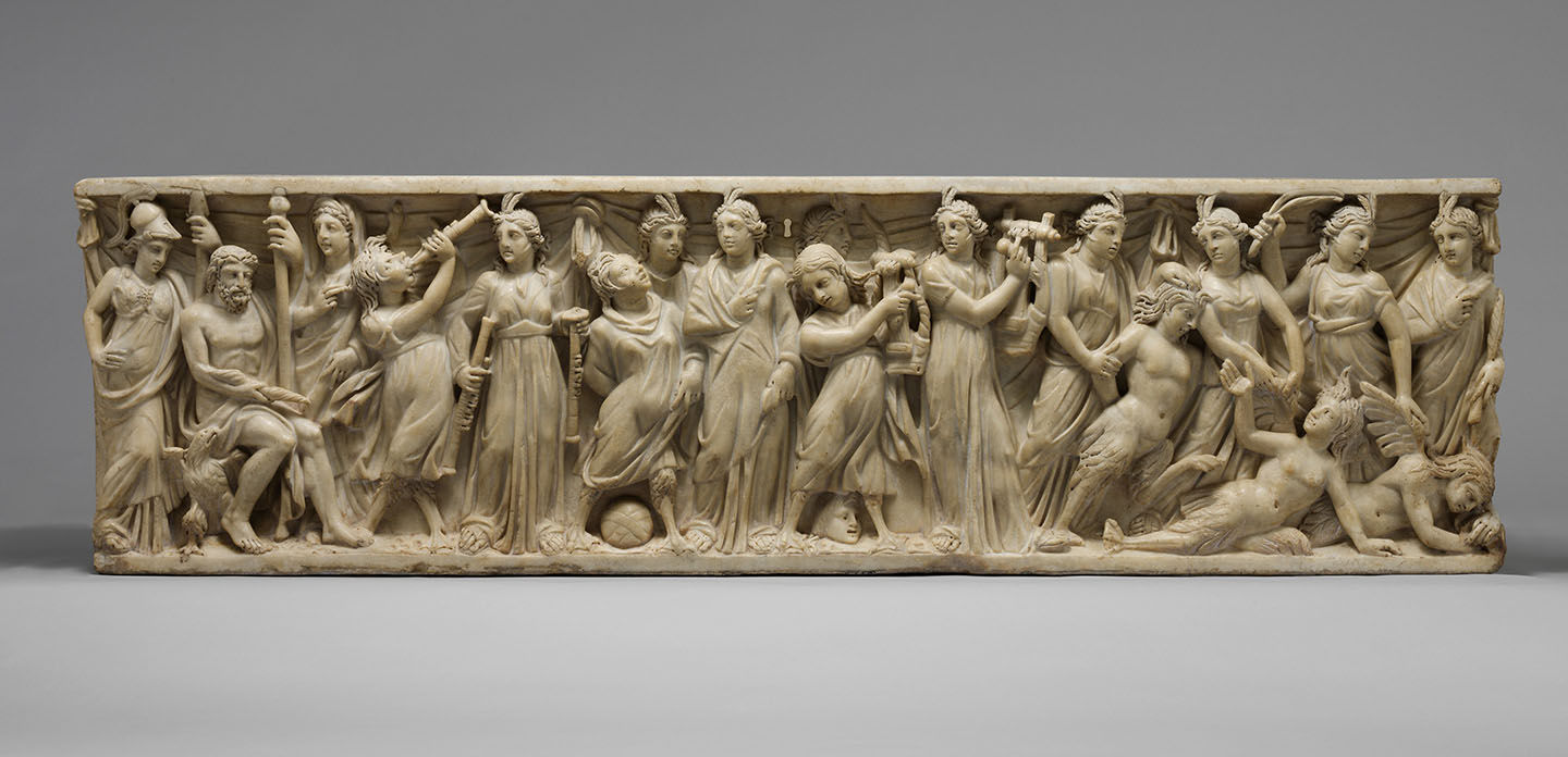 A white stone high relief carved sarcophogus depicting a group of women in classical dress holding various artistic or musical instruments, triumphing over three women with mermaid tails and wings, who have been pushed to the ground