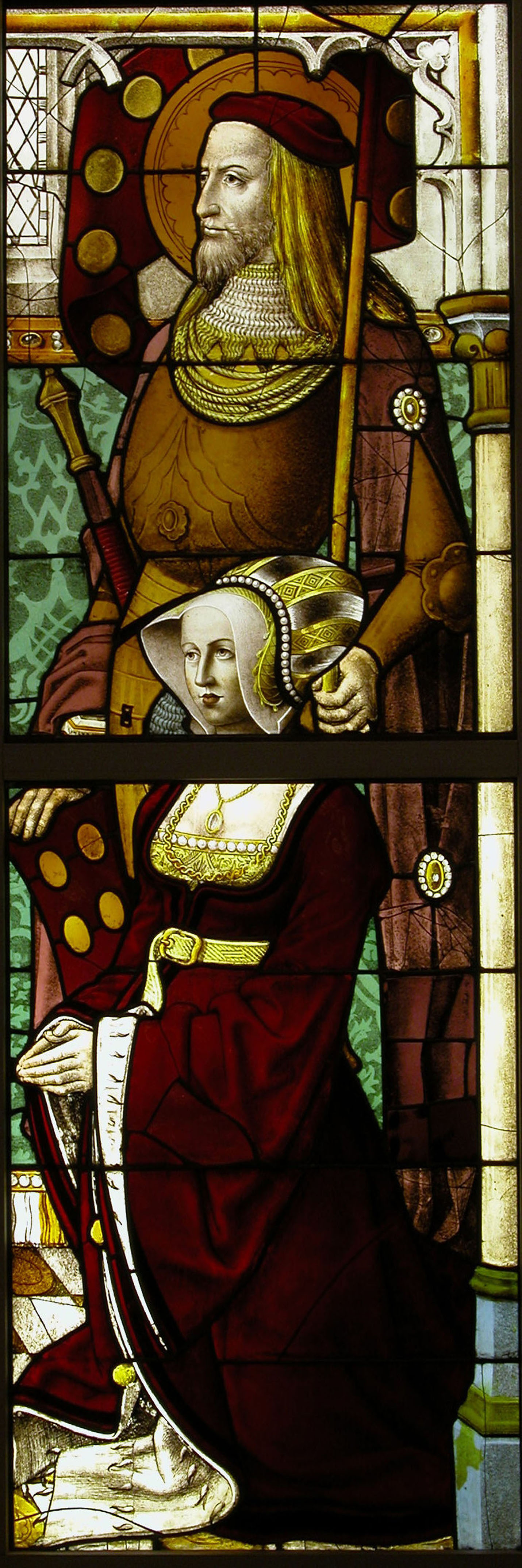 A stained-glass window depicting a man with yellow hair and a pointed beard, wearing a red cap, and holding a staff looking off to the left; a woman in a long red dress is kneeling in front of him, also looking off to the left, with her hands clasped in front of her as if in devotion