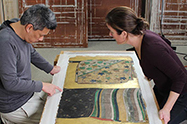 Two conservators examining a golden Japanese scroll