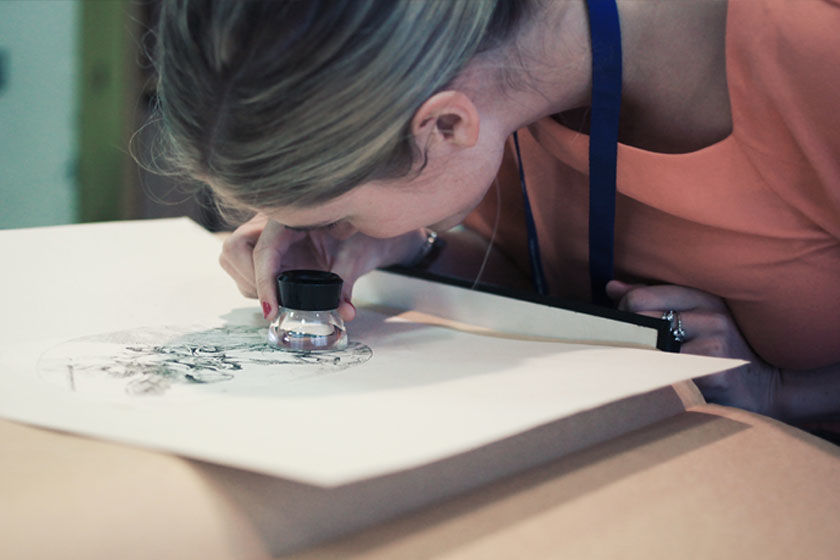 A curatorial staff member looks at an ink drawing using a magnifying lens