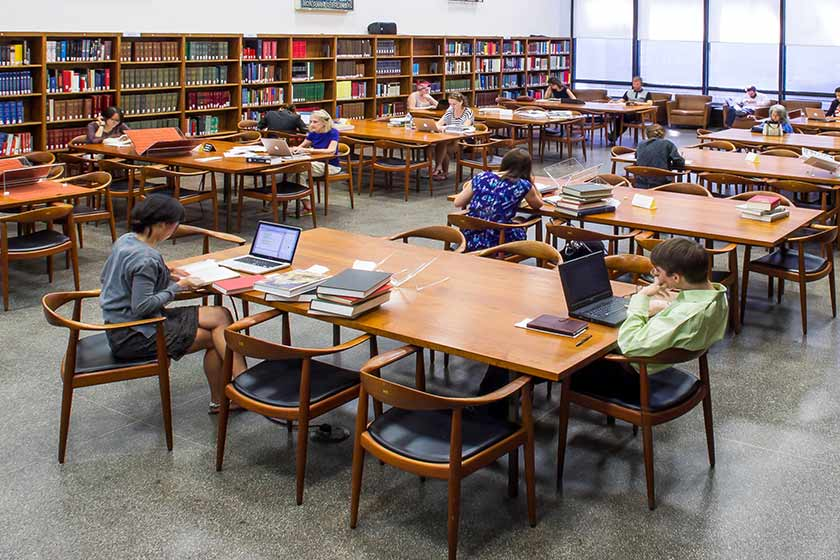 Students study at a long table in Watson Library