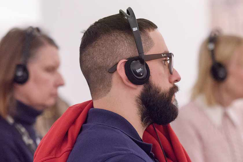 A man listens to a tour guide while using an assistive listening device