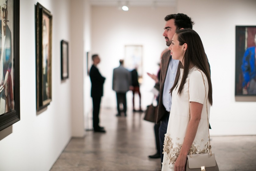 A man and a woman look at paintings in an exhibition gallery