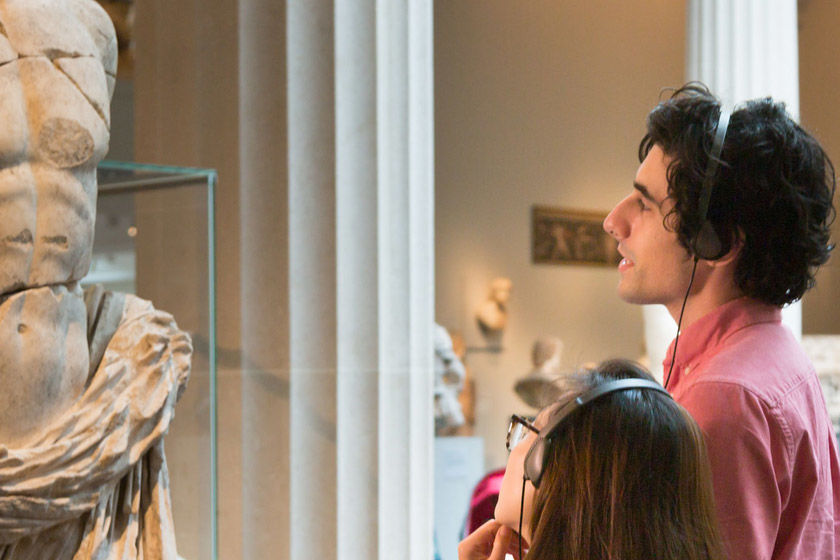 Two visitors use the Audio Guide while looking at a sculpture in the Greek and Roman galleries
