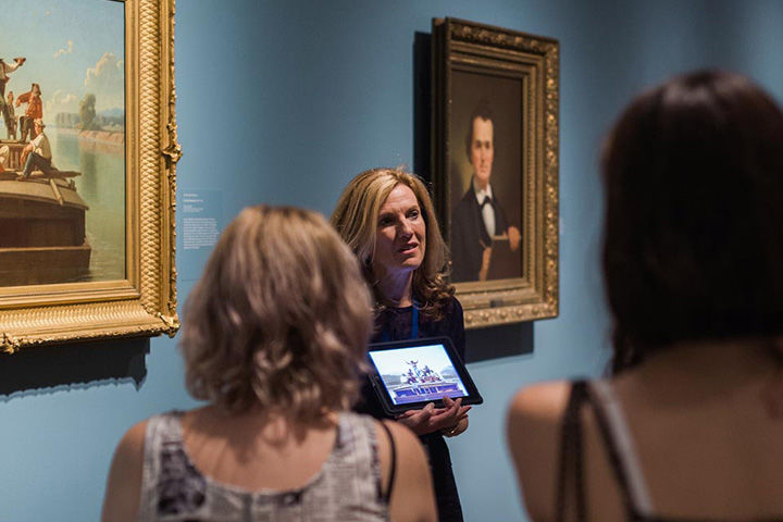 A Museum educator leads a group tour in a gallery of American portraiture