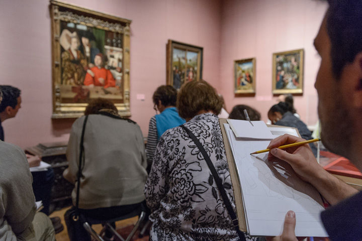 A group of adults draw sketches in the gallery