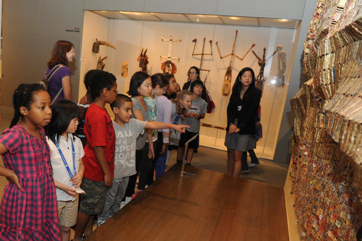 A group of school children explore a gallery and view African art