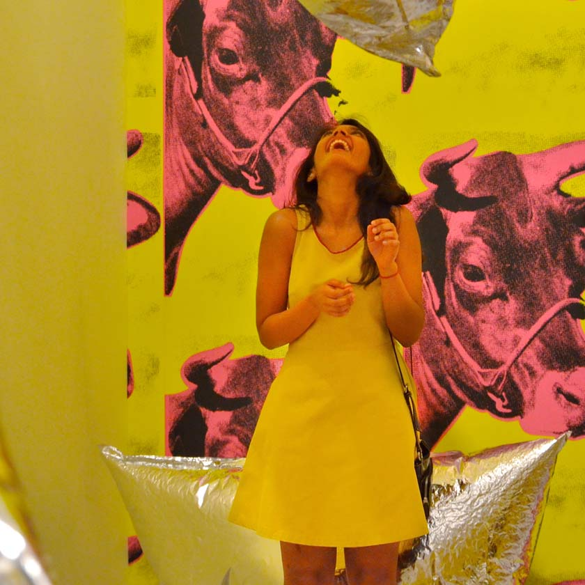 A woman in a yellow dress, laughing, in a gallery decorated with yellow wallpaper decorated with pink bulls