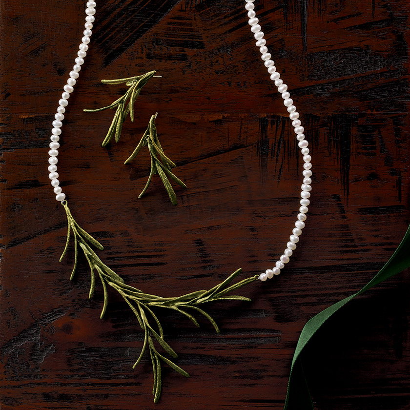 A pearl-and-pine necklace against a wooden background